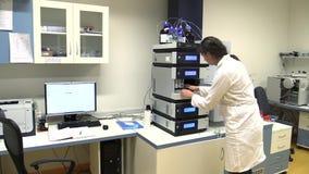 TREBON,捷克, 2015年9月20日:科学的妇女,有海藻的绿叶素,分光仪,小球藻实验室管 股票视频
