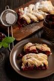 Treccia casalinga della pasta sfoglia della ciliegia, su fondo di legno blu fotografia stock