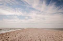 Treccia della sabbia che entra in mare di Azov e cielo nuvoloso fotografia stock libera da diritti