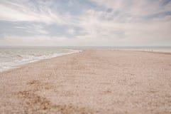 Treccia della sabbia che entra in mare di Azov e cielo nuvoloso fotografie stock