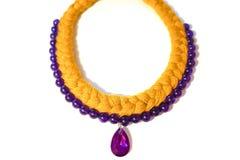 Treccia gialla e porpora della collana da filato con una decorazione fotografie stock libere da diritti