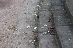 Treden en grondhoogtepunt met gebroken glas en flessen stock afbeelding