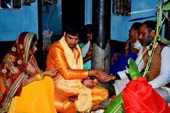 Treditional tillbe av guden som utför vid en indisk familj arkivbilder