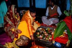 Treditional tillbe av guden som utför vid en indisk familj Familjen uthärda en indisk klänning i suffronfärg fotografering för bildbyråer