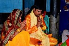 Treditional tillbe av guden som utför vid en indisk familj Familjen uthärda en indisk klänning i suffronfärg arkivbild