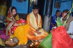 Treditional tillbe av guden som utför vid en indisk familj Familjen uthärda en indisk klänning i suffronfärg arkivfoton