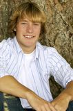 By the Tree. Young blond teenage boy sitting beside a tree stock photos