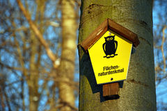 On a tree attached yellow sign with the lettering `Areas Natural Monument` in German language Royalty Free Stock Photos