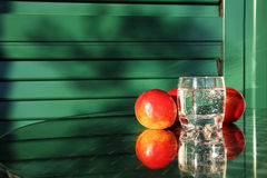 Tree big nectarines and a glass of water on a table Royalty Free Stock Images