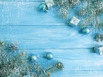 Tree branch, holiday greeting season border creative , celebration card snow on a blue wooden frame. Tree branch, ball snow on a blue wooden background, holiday royalty free stock image
