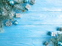 Tree branch, season ball, snow on a blue wooden background, frame royalty free stock images