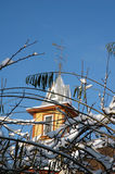 Tree branches covered by snowwith house tower Royalty Free Stock Images