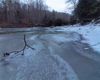 Tree Branches Frozen In Ice. Frozen River with Tree Branches and Twigs frozen into the ice, Hogback Ridge Ohio stock photo