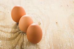Tree brown chicken eggs. Tree brown chicken eggs on wooden table. Focus on middle egg Royalty Free Stock Photo