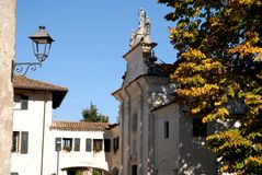 Tree and castle church of St. Nicholas in the village of Strassoldo Friuli (Italy) Royalty Free Stock Images