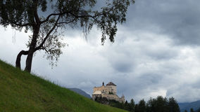 Tree, Castle and Clouds (Tarasp, Graubunden, Switzerland). Tarasp is a gorgeous village in the canton of Graubünden, Switzerland. It is dominated by the Stock Photos