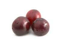 Tree cherries on white background with water drops. Tree deep colored red cherries with water drops. Lie next to each other. Isolated Royalty Free Stock Image