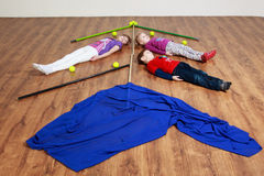 Tree children are lying on the floor between sticks, flags and b Stock Images