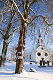 Tree and church in a white winter landscape Royalty Free Stock Photo