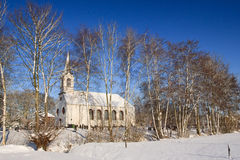 Tree and church in a white winter landscape Stock Photography
