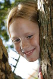 Tree climber. A portrait of a beautiful blond child peeking through the branches of a tree Royalty Free Stock Photos