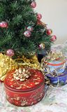 Tree and cookie tins. New artificial tree decorated and cookies tins around Stock Image
