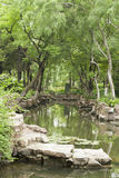 A tree-covered stream. In a chinese traditional garden Stock Photos