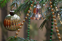 Tree decorated with toys and beads for Christmas. Gold ball and a silver bell with multi-colored beads royalty free stock image