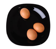 Tree eggs on a black plate Stock Images
