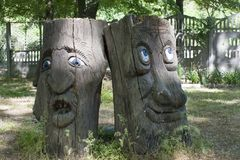 A tree with a face in the middle of the grass. stock image