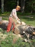 Tree felling: lumberjack chainsawing fallen tree. A lumberjack chainsawing a fallen tree trunk into firewood Royalty Free Stock Photo