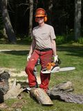 Tree felling: lumberjack man with chainsaw. A lumberjack with chainsaw standing amid firewood Royalty Free Stock Image