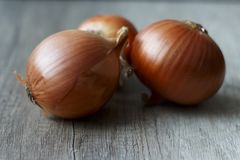 Tree fresh, full of vitamins onions lay on the table. Three onions on the table Stock Photography
