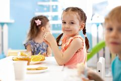 Tree funny kids eating fruits in day care centre. Tree funny children eating fruits in day care centre stock images