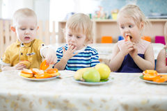 Tree funny kids eating fruits in day care centre Royalty Free Stock Photo