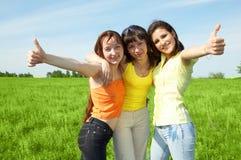 Tree girlfriend in green field. Three girlfriend in green field under blue sky Stock Photography