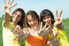 Tree girlfriend in green field. Three girlfriend in green field under blue sky Royalty Free Stock Photos