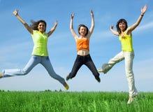 Tree girlfriend jump in green field. Three girlfriend jump in green field under blue sky Stock Photos