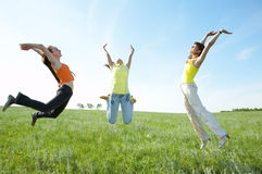 Tree girlfriend jump in green field Stock Images