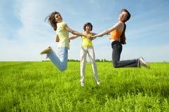 Tree girlfriend jump in green field. Three girlfriend jump in green field under blue sky Royalty Free Stock Photography
