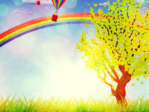 Tree on grass field. Green grass field with a tree, rainbow and hot air balloons in the sky Stock Photo
