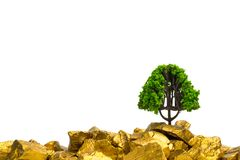 Tree growing on pile of gold nuggets, growth business finance investment concept. Idea stock photography