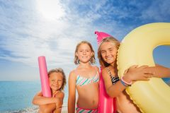 Tree happy girls standing together at the beach. Close-up portrait of tree happy age-diverse girls standing together at the beach, holding rubber ring, mattress royalty free stock photography