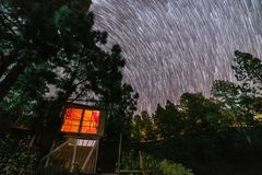 Tree house in the middle of nature under a circular spiral stars trail royalty free stock photo
