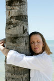 Tree Hugger. Woman holding on to a tree trunk Royalty Free Stock Image