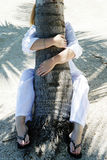 Tree Hugger. Female hugging a palm tree trunk on the beach Royalty Free Stock Photography