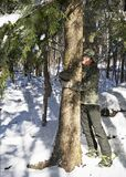 Tree Hugger under Snow-Covered Branches in Forest