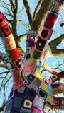 Tree with a jumper on. A tree in Stratford Upon Avon England covered in a crocheted colourful jumper Stock Photo