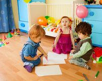 Tree kids drawing sitting on the floor Stock Images
