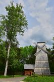 A tree leaning towards a windmill in an old manor house royalty free stock photography